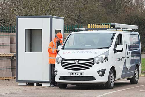operative speaking to a driver in a van outside a site cabin