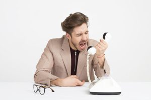 person shouting at a telephone