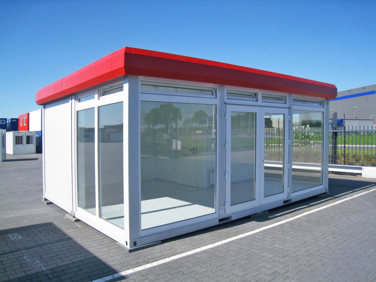 large red and white portable retail cabins in car park with red roof