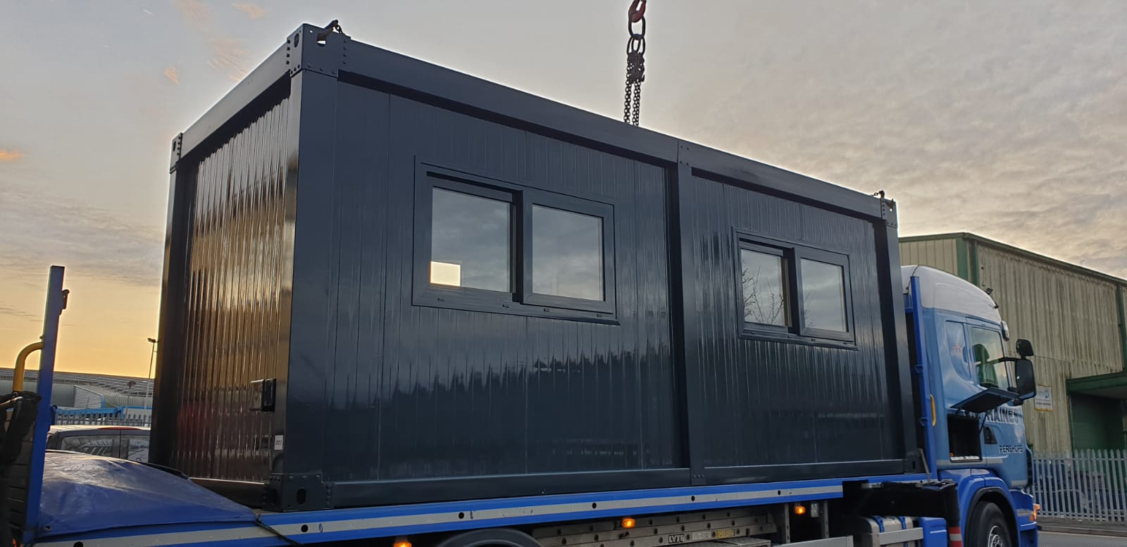grey steel security cabin on the bed of a hiab lorry