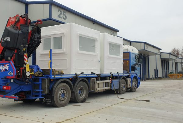 two white kiosks sitting on a hiab lorry bed